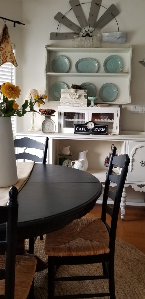 kitchen table painted black with a black ladder back chair in front of an antique white hutch and sideboard