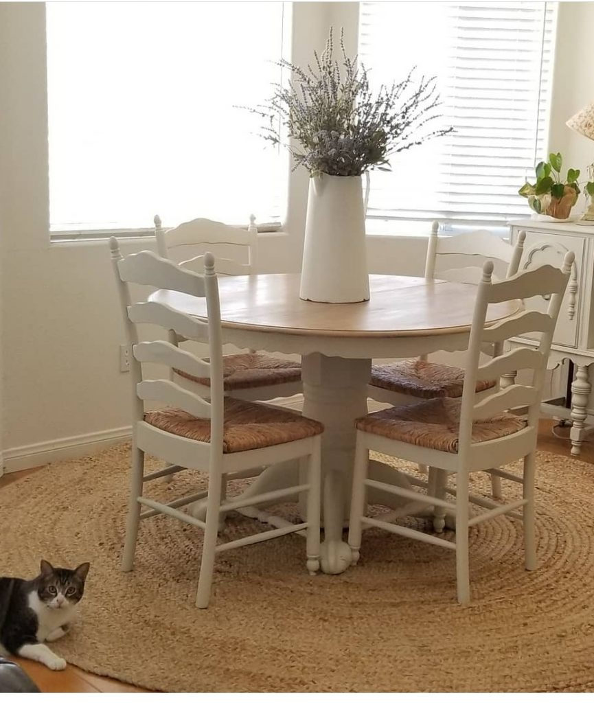 White round kitchen table with ball and claw white base, and natural table top. Surrounded by 4 white ladderback chairs with woven cane seating.
